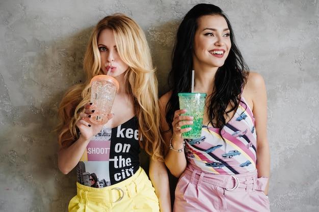 Deux filles, une brune et une blonde, en pantalon coloré. boire des cocktails.