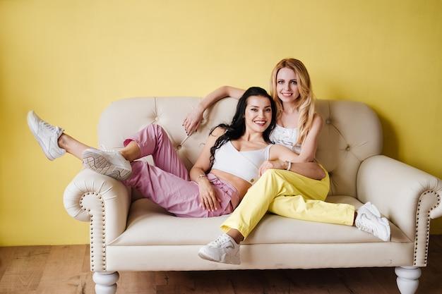 Deux filles, une brune et une blonde, en pantalon coloré sur un canapé léger sur fond de mur jaune.