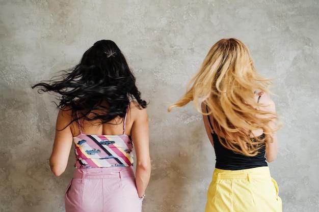 Deux filles, une brune et une blonde, en pantalon coloré. copines sur un mur texturé. couleur de cheveux.
