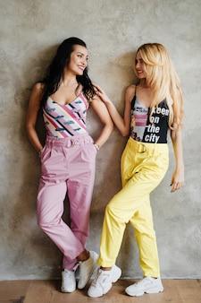 Deux filles, une brune et une blonde, en pantalon coloré. copines sur un mur texturé.