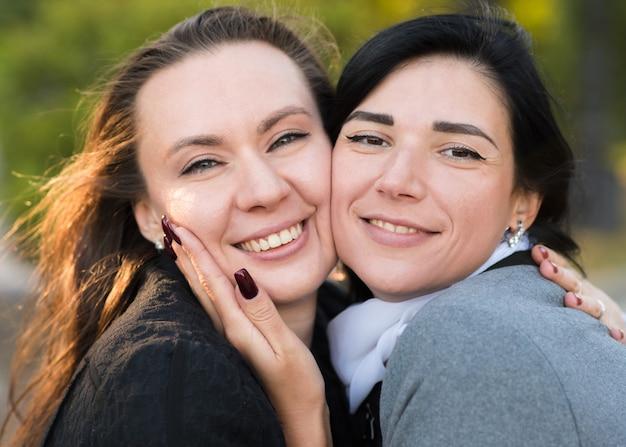 Deux filles brunes caucasiennes s'embrassent dans le parc ensoleillé d'automne. heureux couple de lesbiennes, lgbt, lgbtq.