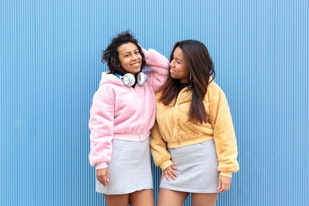 Deux filles brunes drôles posant ensemble sur un fond bleu. espace pour le texte. concept d'amitié.