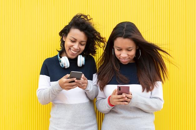 Deux filles brunes souriantes sur fond jaune. ils portent la même robe et utilisent leurs téléphones intelligents. espace pour le texte.