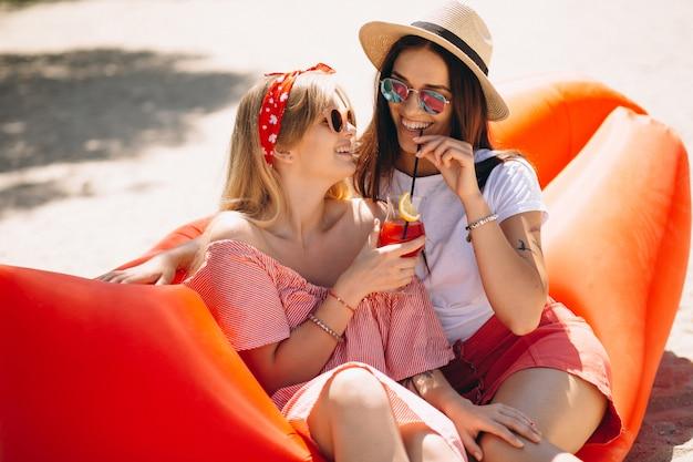 Deux filles buvant des cocktails à la plage