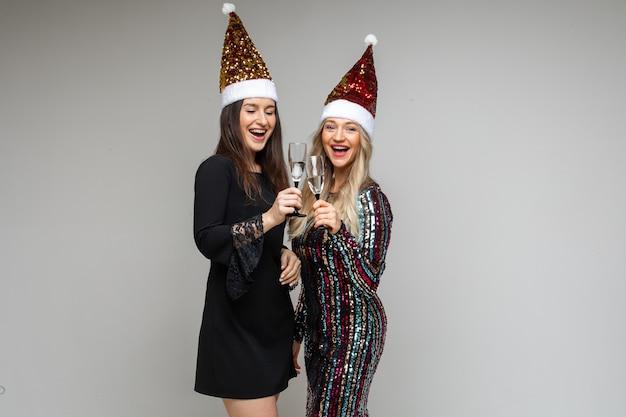 Deux filles en chapeaux de père noël avec des boissons alcoolisées.