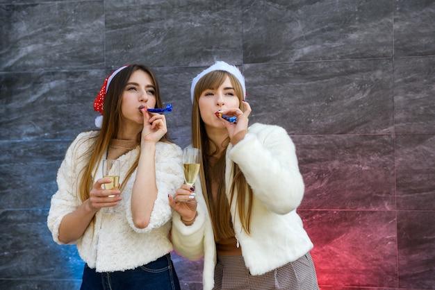 Deux filles en chapeaux de père noël avec des verres de champagne célèbrent le nouvel an