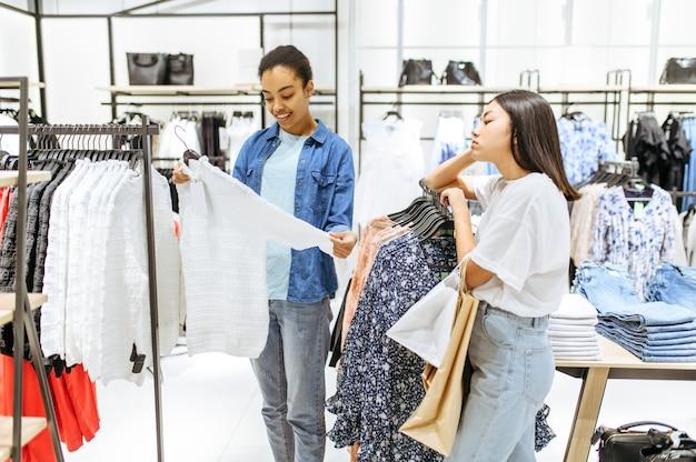 Deux filles choisissant un pantalon dans un magasin de vêtements
