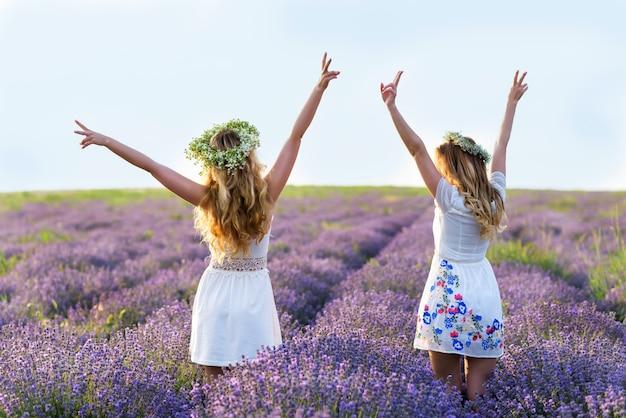 Deux filles dans un champ de lavande. femmes heureux s'amuser. portrait de la journée de l'amitié