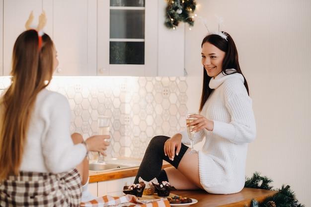 Deux filles dans un environnement familial confortable dans la cuisine avec du champagne à la main pour noël. les filles souriantes boivent du champagne lors d'une soirée festive