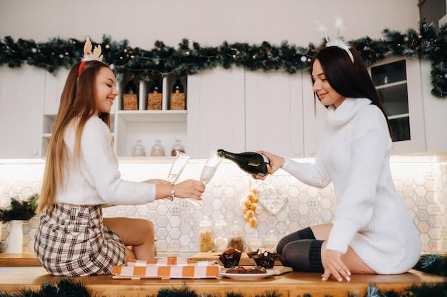 Deux filles dans un environnement familial confortable dans la cuisine versent du champagne pour noël. les filles souriantes boivent du champagne lors d'une soirée festive