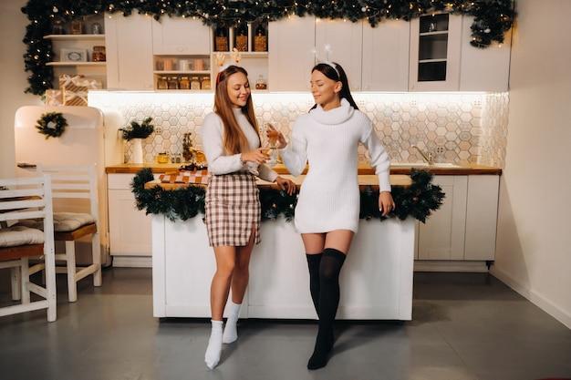 Deux filles dans un environnement familial confortable avec du champagne dans les mains à noël. les filles souriantes boivent du champagne lors d'une soirée festive