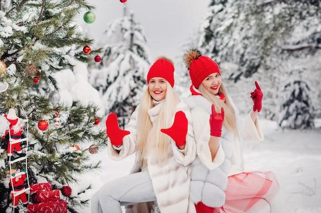 Deux filles dans la forêt d'hiver près d'un arbre de noël décoré.