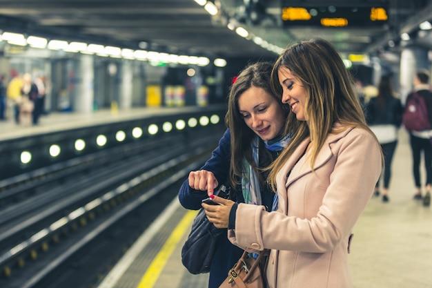Deux filles dans le métro londonien attendant le train.