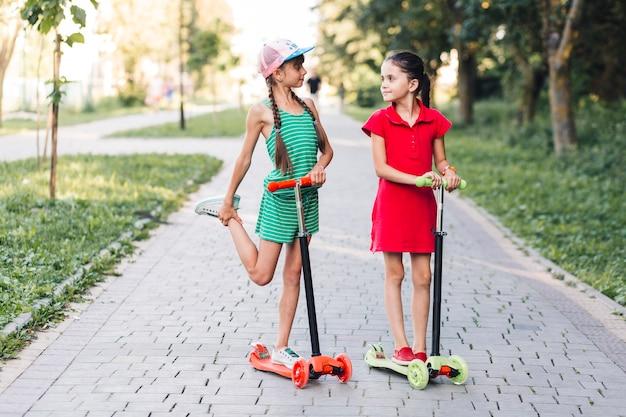 Deux, filles, debout, pousser, scooter, dans parc