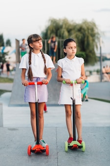 Deux, filles, debout, sur, rouge, et, vert, pousser, scooter, dans parc