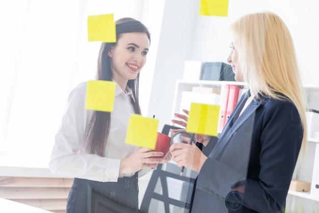 Deux filles discutant dans le bureau. les filles sont un dialogue près d'un tableau transparent avec des autocollants.