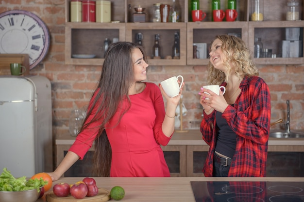 Deux filles discutant avec une tasse de café dans la cuisine