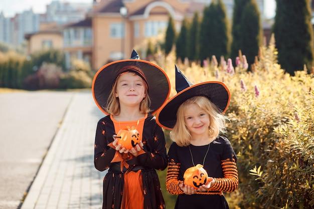Deux filles drôles en costumes d'halloween tiennent des lanternes jack o dans leurs mains à l'extérieur en automne ...