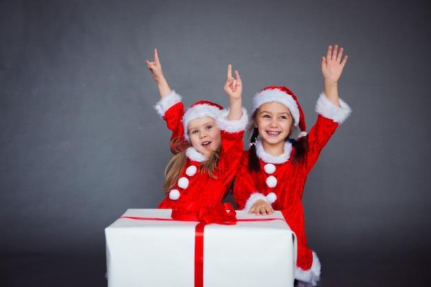 Deux filles drôles dans des chapeaux et des vêtements de père noël s'amusant avec un grand ruban rouge de boîte-cadeau