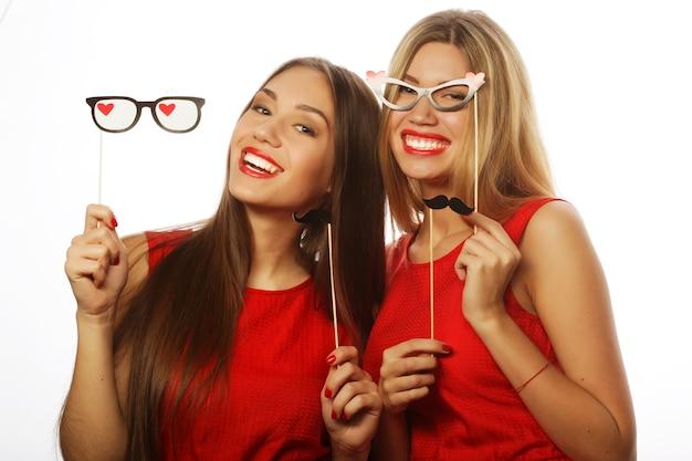 Deux filles élégantes meilleurs amis vêtus d'une robe rouge prête pour la fête, sur blanc