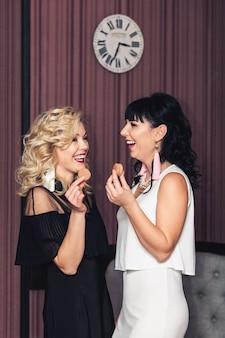 Deux filles élégantes en robes avec des boucles d'oreilles faites à la main tiennent des macarons dans leurs mains et rient.