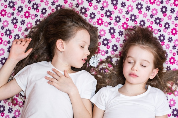 Deux filles endormies et un réveil blanc entre les deux. vue de dessus