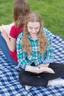 Deux filles étudient à l'extérieur sur une couverture de pique-nique
