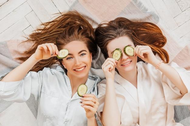 Deux filles fabriquent des masques de beauté pour le visage et les cheveux faits maison. concombres pour la fraîcheur de la peau autour des yeux. les femmes prennent soin d'une peau jeune. les copines rient à la maison allongées sur le sol sur des oreillers.