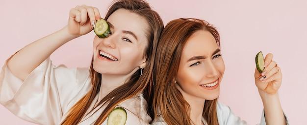 Deux filles fabriquent des masques de beauté pour le visage faits maison. concombres pour la fraîcheur de la peau autour des yeux. les femmes prennent soin d'une peau jeune. copines riant et s'amusant au spa sur fond rose