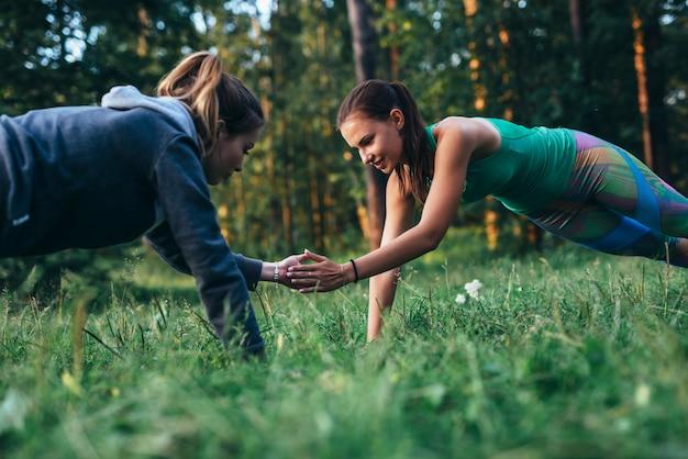 Deux filles, faire, copain, séance entraînement, dehors, exécuter, push-ups, pour, applaudir, sur, herbe
