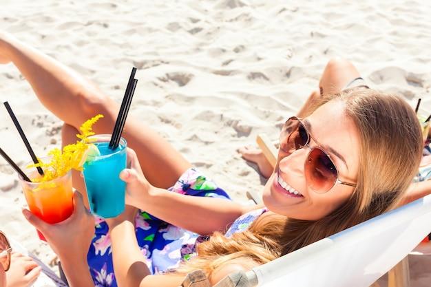 Deux filles ou femme buvant des cocktails au club de plage et assis sur une chaise longue