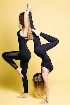 Deux filles flexibles en costume sportif noir posant sur un mur jaune.