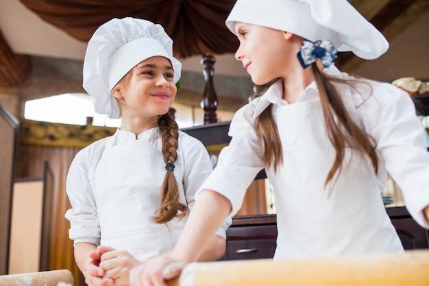 Deux filles font de la pâte à la farine.