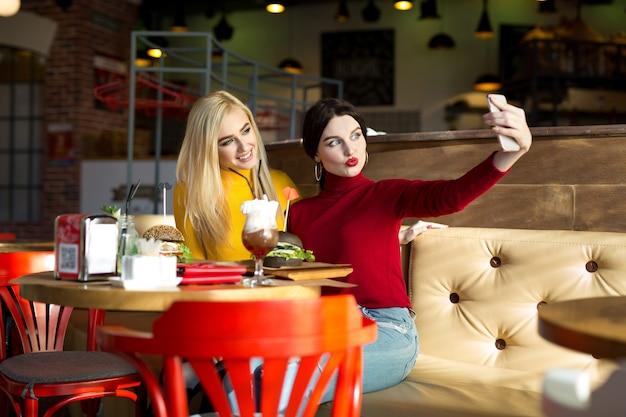 Deux filles gaies joyeuses prenant un selfie assis ensemble au café