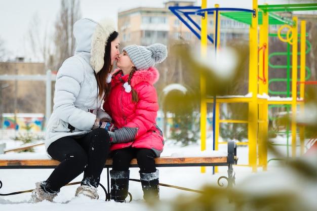 Deux filles heureuse, mère et fille, assis sur un banc dans une aire de jeux dans le parc de la ville.