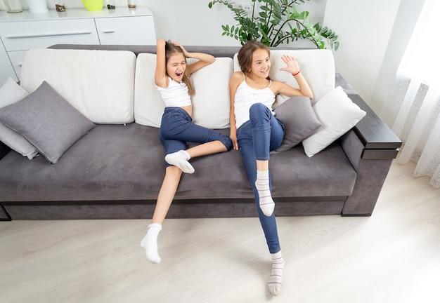 Deux filles heureuses s'amusant sur un canapé dans le salon