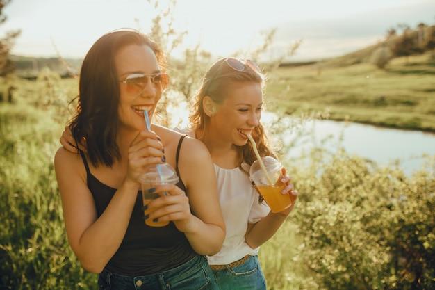 Deux filles heureuses s'amusent, boivent un cocktail dans une tasse en plastique avec de la paille dans des lunettes de soleil au coucher du soleil, expression faciale positive, vacances en plein air et concept de bonheur