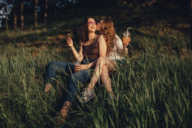 Deux filles heureuses s'amusent, s'assoient sur l'herbe, s'embrassent sur la joue, dans des lunettes de soleil, au coucher du soleil, expression faciale positive, en plein air
