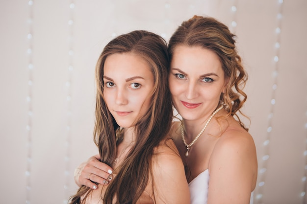 Deux filles heureuses sourient. portrait de femme embrassant. relations dans la famille, amis, soeurs, couple amoureux