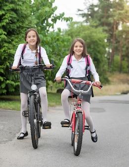 Deux filles heureuses en uniforme allant à l'école le matin