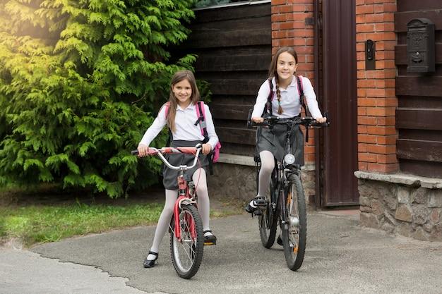 Deux filles heureuses en uniforme scolaire avec des sacs allant à l'école à vélo