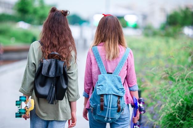 Deux filles hipster avec planche à roulettes à l'extérieur à la lumière du coucher du soleil. closeup skatebords dans les mains féminines. femmes sportives actives s'amusant ensemble dans le skate park.