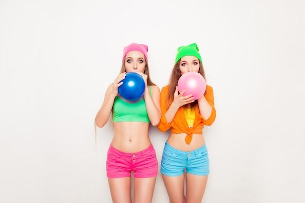 Deux filles hipster se préparent pour la fête et soufflent des ballons