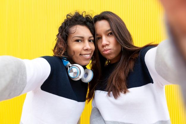 Deux filles hispaniques drôles prenant selfie photo sur téléphone mobile. ils sont isolés sur fond jaune. concept d'amitié.