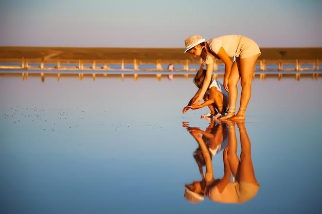 Deux filles incroyablement belles dans des tenues inhabituelles sur un magnifique lac salé transparent recherchent quelque chose dans une surface brillante
