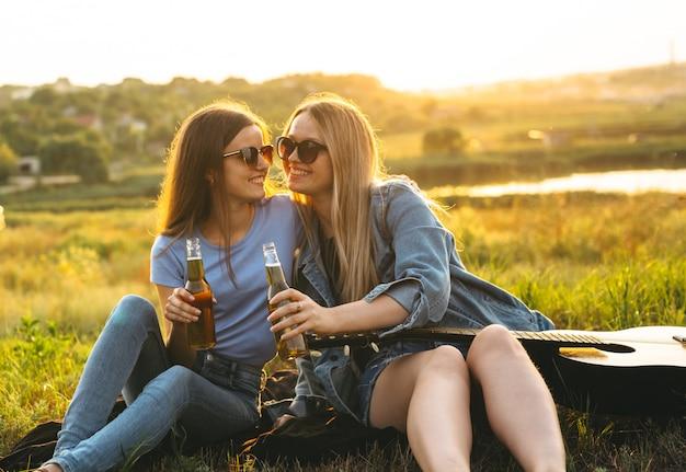 Deux filles joyeuses et jeunes amis avec des lunettes de soleil, buvant de la bière et profitant du temps passé ensemble au coucher du soleil.