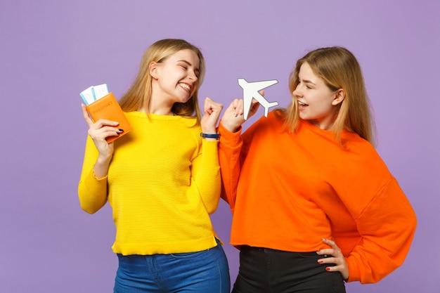 Deux filles jumelles blondes heureuses dans des vêtements colorés tenant un passeport, un billet d'embarquement, un avion en papier isolé sur un mur bleu violet. concept de mode de vie familial de personnes.
