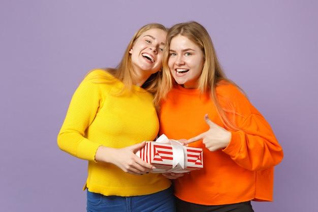Deux filles jumelles blondes heureuses dans des vêtements vifs tenant une boîte cadeau à rayures rouges avec un ruban cadeau isolé sur un mur bleu violet. anniversaire de la famille des gens, concept de vacances.