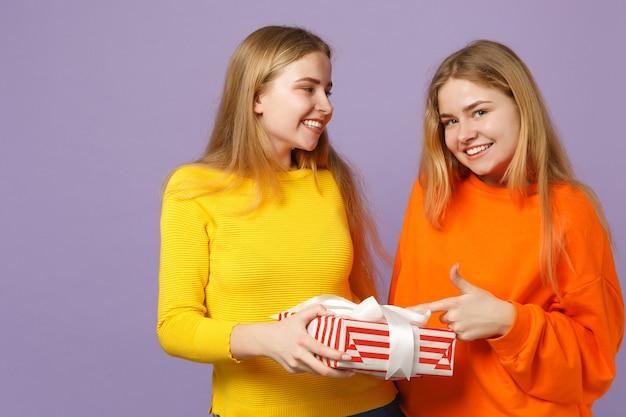 Deux filles jumelles blondes mignonnes dans des vêtements vifs tenant une boîte cadeau à rayures rouges avec un ruban cadeau isolé sur un mur bleu violet. anniversaire de la famille des gens, concept de vacances.