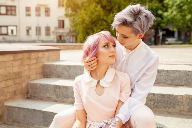 Deux filles lesbiennes assis sur les escaliers dans la ville
